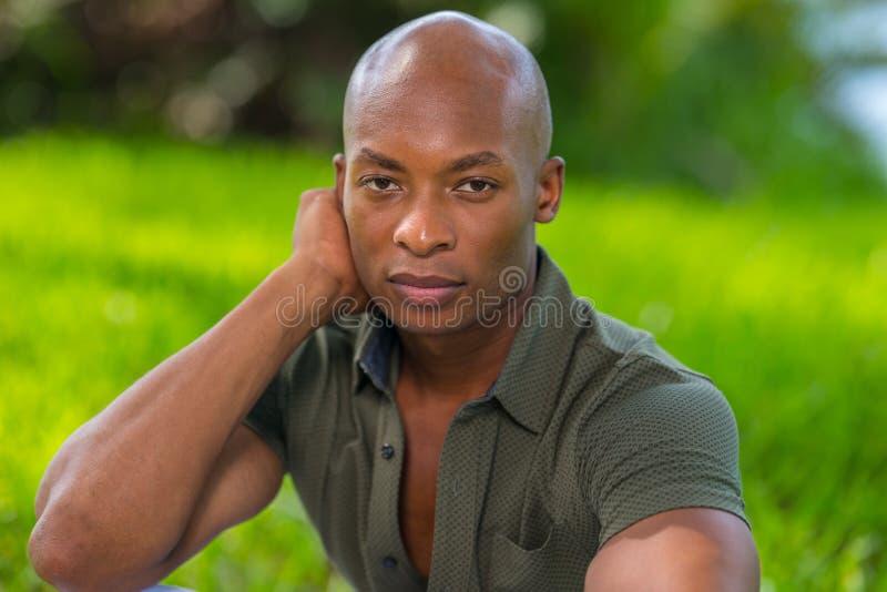 Foto de un hombre hermoso que mira la cámara con la cabeza que descansa sobre su mano Fondo colorido verde vibrante en el parque fotos de archivo