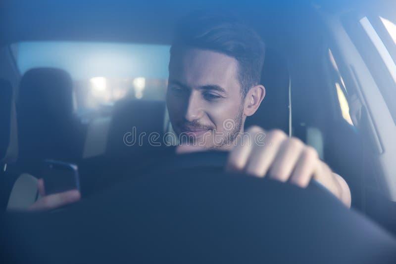 Foto de un hombre hermoso que usa el teléfono móvil mientras que conduce imagenes de archivo