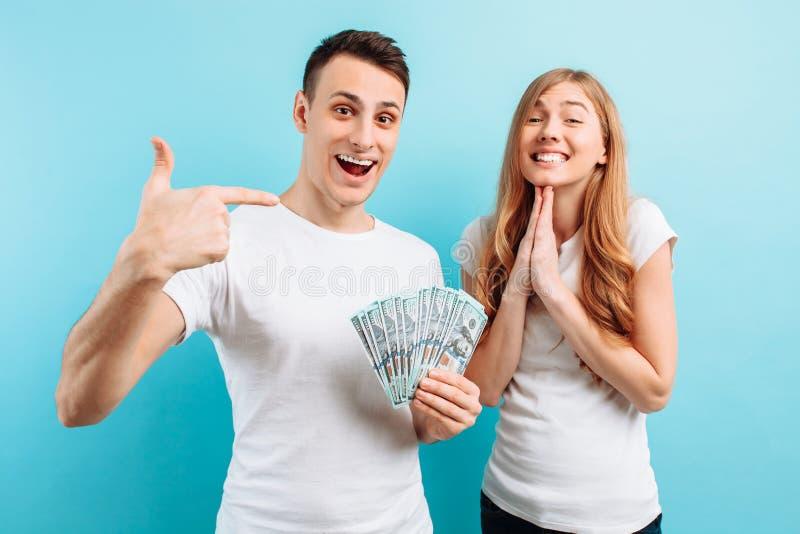 Foto de un par joven feliz en el amor, el hombre y la mujer, vestidos sosteniendo el dinero en sus manos, en un fondo azul fotos de archivo libres de regalías