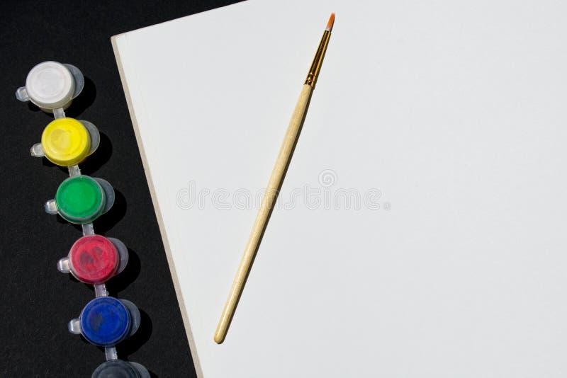 Foto de un pedazo de papel de dibujo con un cepillo al lado de la pintura en un fondo negro Visión desde arriba imagenes de archivo