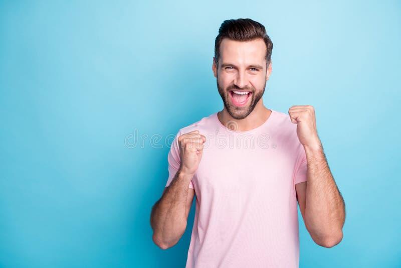 Foto de un tipo atractivo emociones extáticas ganan premio de lotería gritando regocijo alzando los puños usan rosa casual foto de archivo libre de regalías