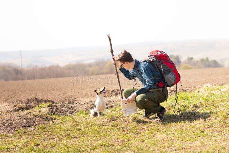 Foto de un turista joven y de su perro, caminando en el campo fotos de archivo libres de regalías