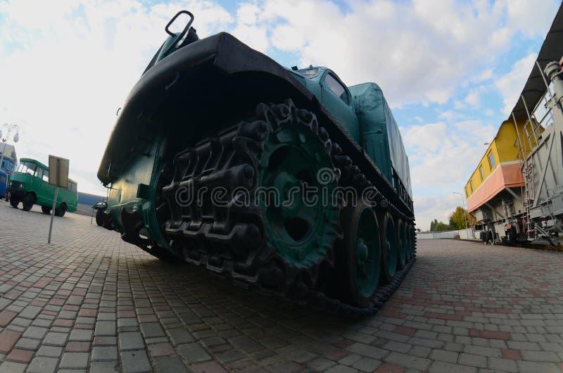Foto de un vehículo ligero blindado verde ruso en una vía de oruga entre los trenes ferroviarios La distorsión fuerte del fisheye imagen de archivo