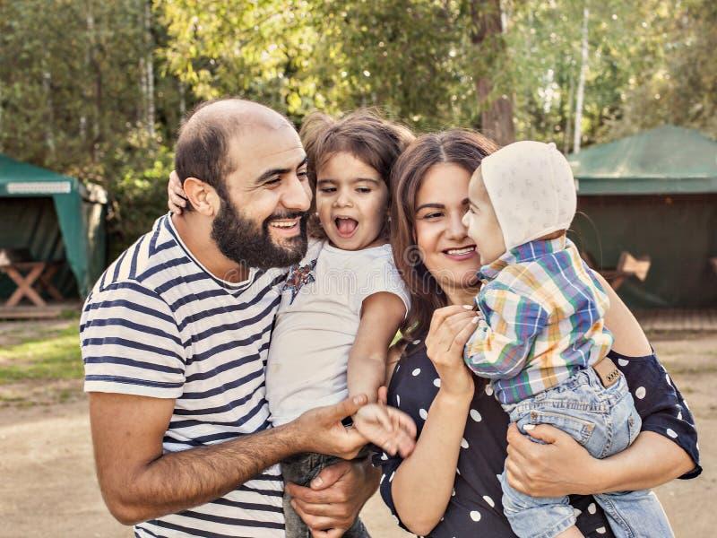 Foto de una familia feliz La muchacha recién nacida y de cuatro años del papá de la mamá pasa tiempo en el parque en verano imagen de archivo