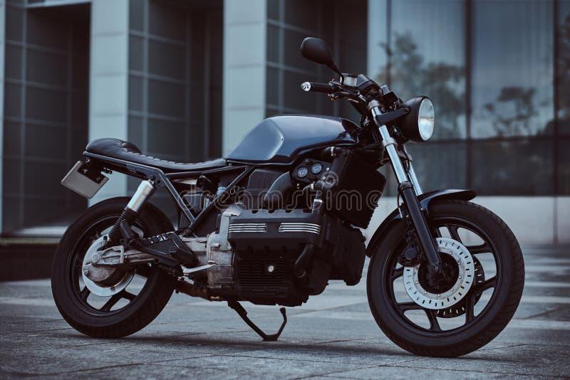 Foto de una motocicleta retra por encargo contra rascacielos imagen de archivo