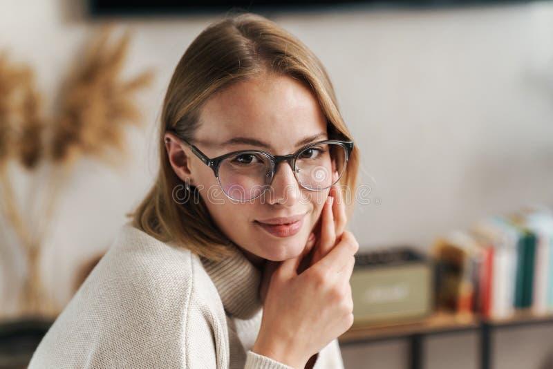 Foto de una mujer agradable y complacida en anteojos mirando la cámara fotos de archivo libres de regalías