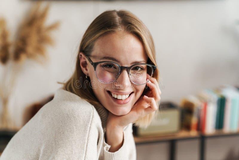 Foto de una mujer atractiva sonriente en anteojos mirando la cámara imagen de archivo libre de regalías