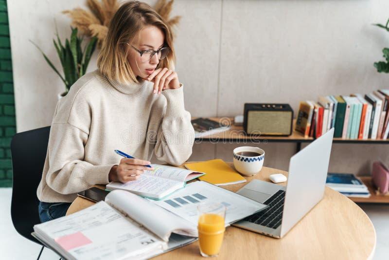Foto de una mujer haciendo notas en el libro de ejercicios y usando una laptop fotografía de archivo libre de regalías