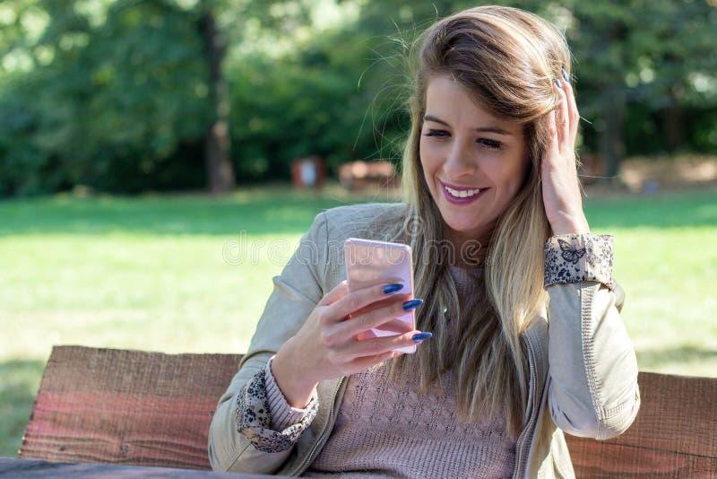 Foto de una mujer que usa el teléfono elegante fotos de archivo libres de regalías