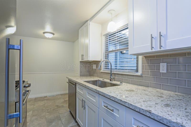 Foto de una pequeña cocina compacta con los gabinetes blancos de la coctelera fotos de archivo