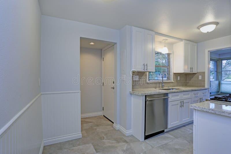 Foto de una pequeña cocina compacta con los gabinetes blancos de la coctelera fotos de archivo libres de regalías