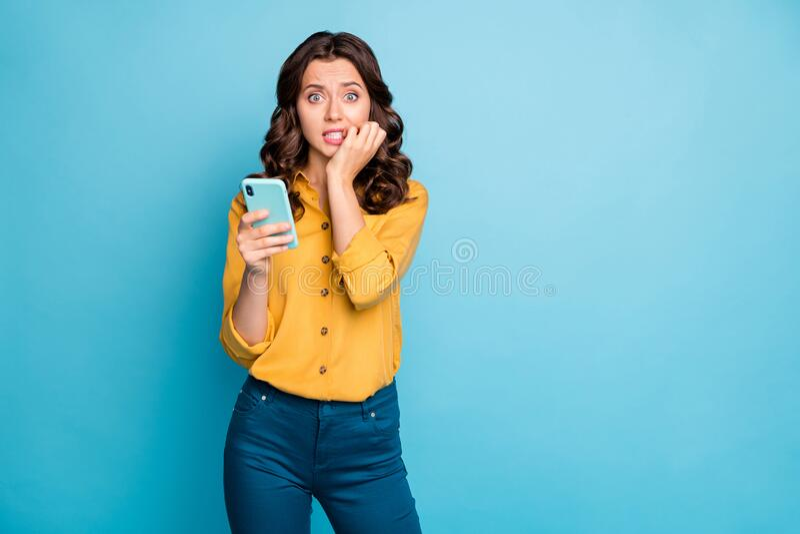 Foto de una señora guapa sosteniendo manos telefónicas mordiendo los ojos llenos de miedo post negativo comentarios usando camisa fotografía de archivo