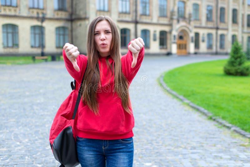 Foto de zombar o moderno adolescente de assobio unpleased em calças de brim ocasionais e na camiseta da camiseta que dá os dedos  fotos de stock royalty free