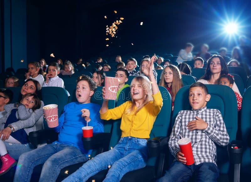 Foto dei bambini che si siedono sulla prima fila del cinema immagini stock