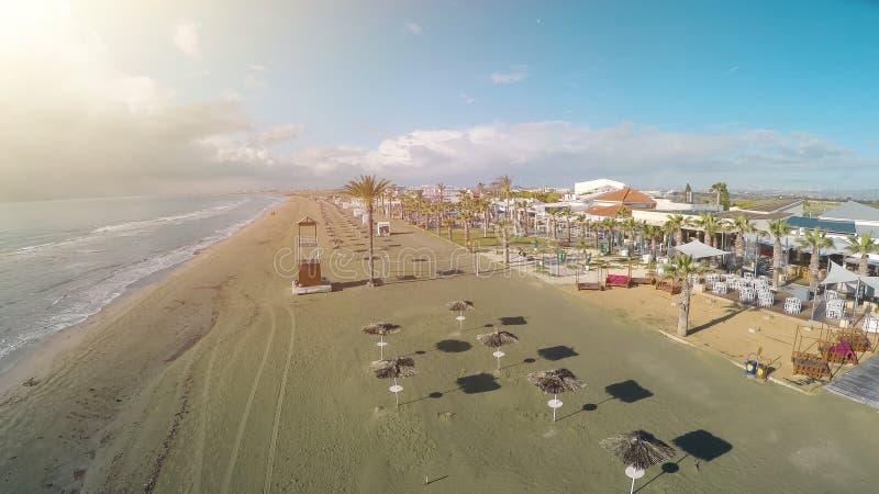 Foto del abejón de la playa de Larnaca en Chipre, los parasoles y los sillones, mar de la paja imagen de archivo libre de regalías