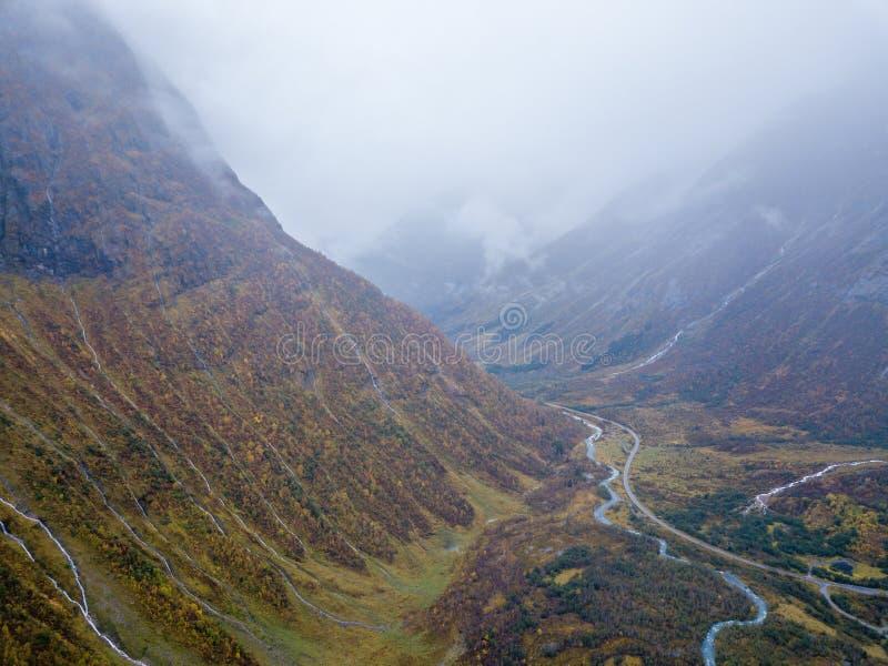 Foto del abejón de varias pequeñas cascadas en montañas con las nubes que las cubren cerca del glaciar de Bøjabreen en Noruega imágenes de archivo libres de regalías