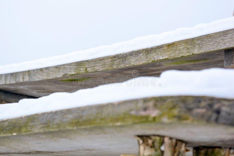 Foto del banco viejo cubierto con nieve en invierno imagenes de archivo