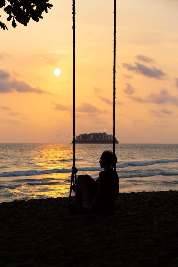Foto del blog del viaje: Silueta de una mujer en un vestido durante puesta del sol con una visi?n sobre el mar con un peque?o isa imagen de archivo libre de regalías