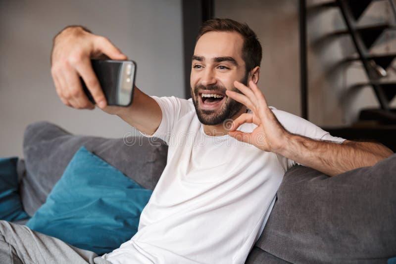 Foto del celibe ottimista che tiene e che prende selfie sul telefono cellulare mentre sedendosi sullo strato in salone immagini stock libere da diritti
