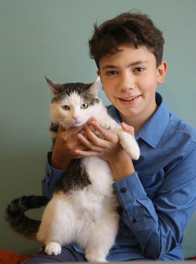 Foto del cierre del gato del abrazo del muchacho del adolescente del amante del gato encima de la foto divertida fotografía de archivo libre de regalías