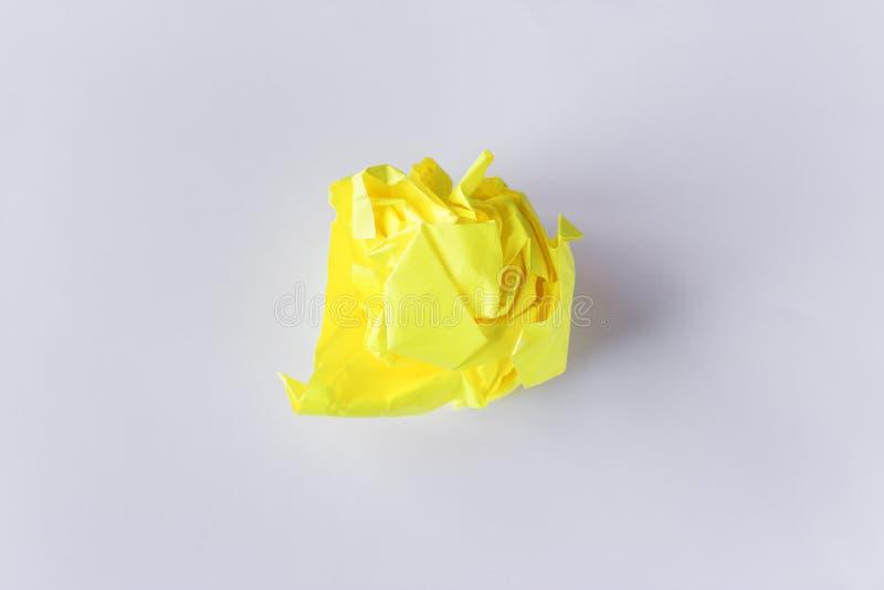 Foto del concepto de la bola de papel amarilla arrugada en el fondo blanco Falta de ideas, sufrimientos creativos fotos de archivo