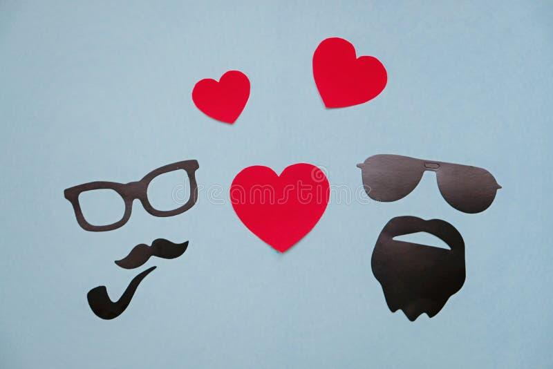 Foto del concepto de la homosexualidad: máscaras masculinas con los corazones en fondo azul foto de archivo