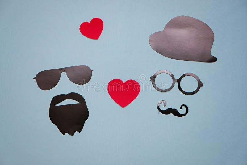 Foto del concepto de la homosexualidad: máscaras masculinas con los corazones en fondo azul fotos de archivo