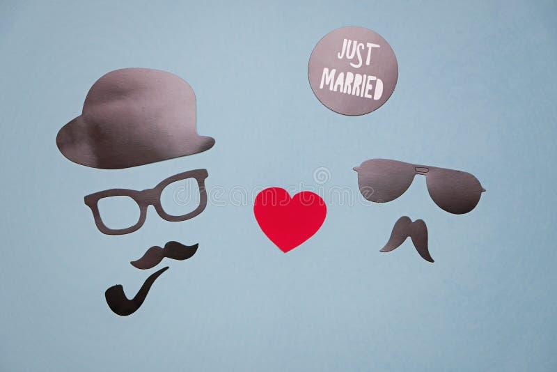 Foto del concepto de la homosexualidad y del matrimonio homosexual: máscaras masculinas con los corazones en fondo azul fotografía de archivo