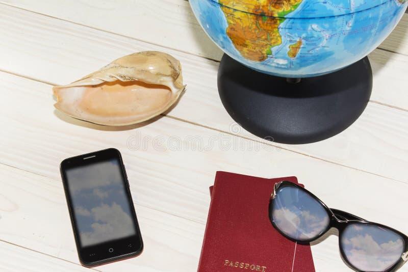 Foto del concepto del turista que acepilla el viaje con el mapa, pasaporte, teléfono móvil fotografía de archivo