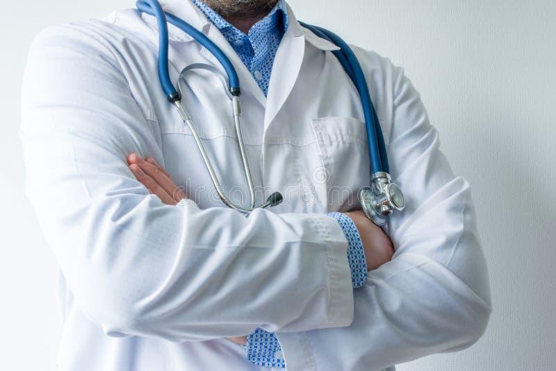 Foto del cuerpo del doctor en la capa blanca del laboratorio con el estetoscopio en su cuello en media vuelta con las manos dobla imagen de archivo