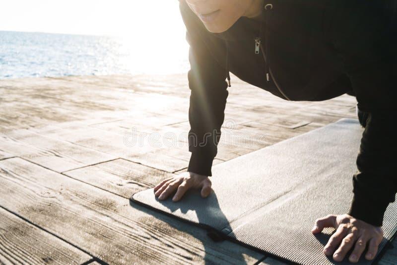 Foto del deportista fuerte 20s en el chándal que miente en la estera de la aptitud y que hace ejercicio del tablón por la playa imagen de archivo