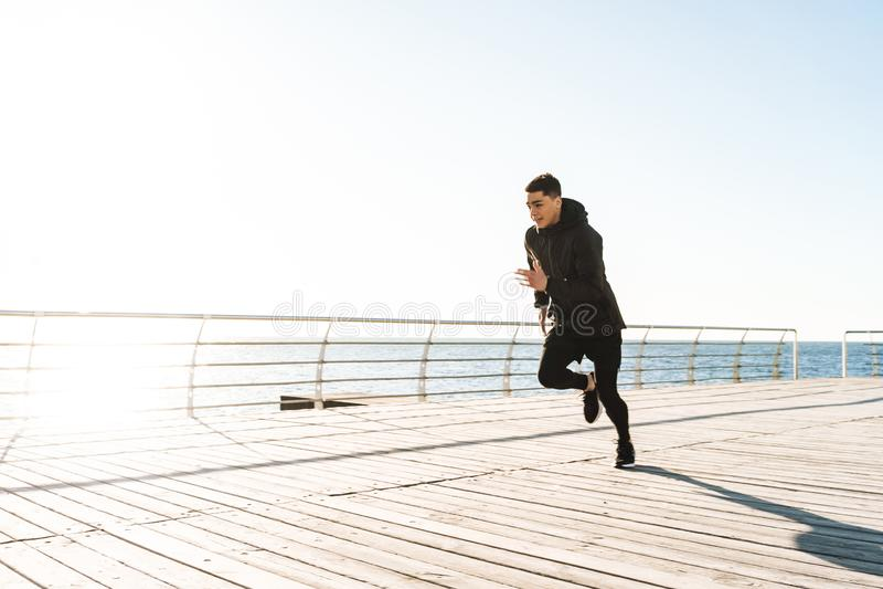 Foto del deportista hermoso que corre por la playa a lo largo del paseo marítimo de madera durante entrenamiento de la mañana imagenes de archivo