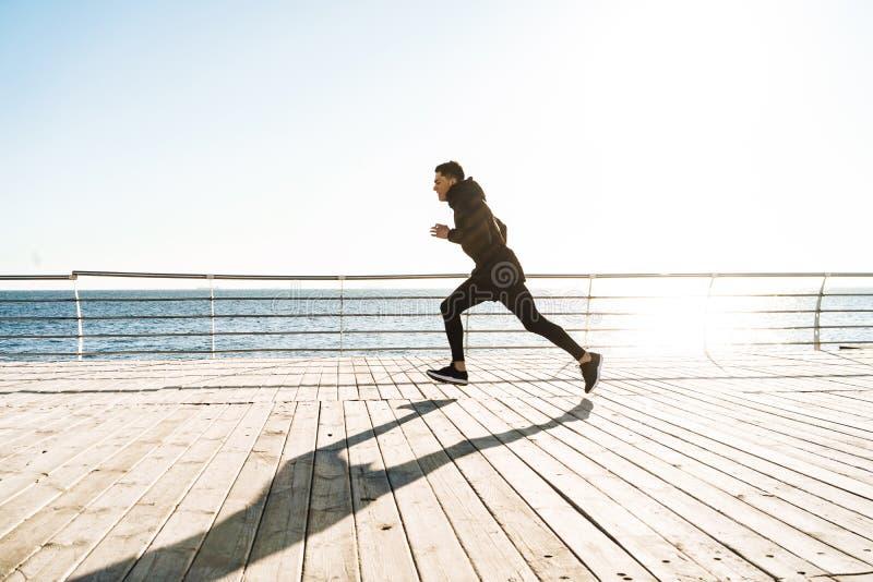 Foto del deportista joven que corre por la playa a lo largo del paseo marítimo de madera durante entrenamiento de la mañana foto de archivo