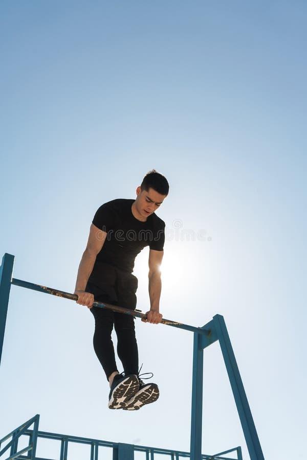Foto del deportista joven que hace la acrobacia en barra gimnástica horizontal durante entrenamiento de la mañana por la playa imagenes de archivo
