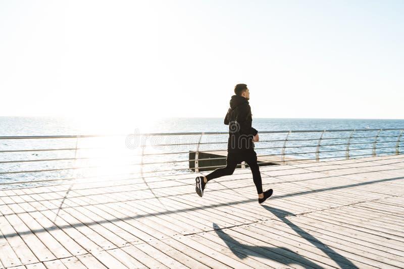 Foto del deportista sano que corre por la playa a lo largo del paseo marítimo de madera durante entrenamiento de la mañana fotos de archivo