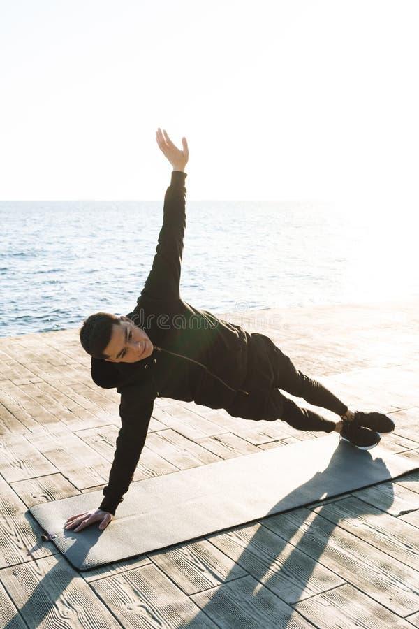 Foto del deportista satisfecho 20s en el chándal que miente en la estera de la aptitud y que hace ejercicio del tablón por la pla imágenes de archivo libres de regalías