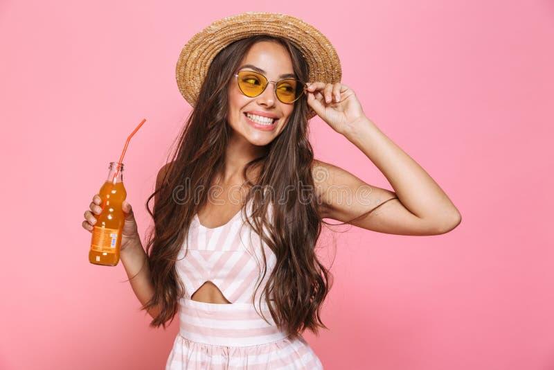 Foto del drin de las gafas de sol de la mujer 20s del encanto que lleva y del sombrero de paja imágenes de archivo libres de regalías
