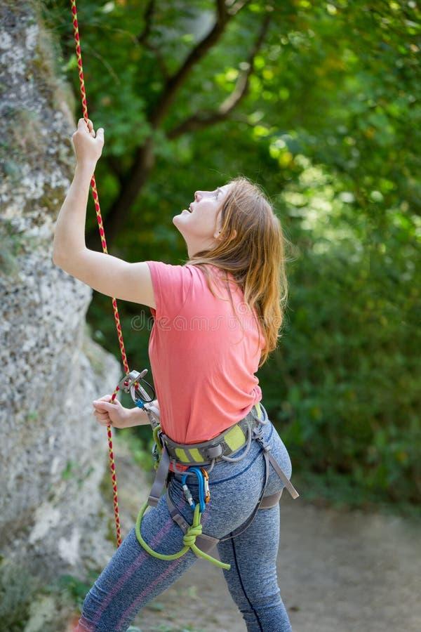 Foto del escalador de roca de la mujer joven con la cuerda de la seguridad en manos de la roca en el fondo de árboles verdes fotografía de archivo