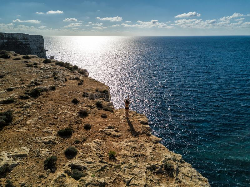 Foto del fuco - una donna in cima alle scogliere dell'isola di Comino, Malta fotografia stock