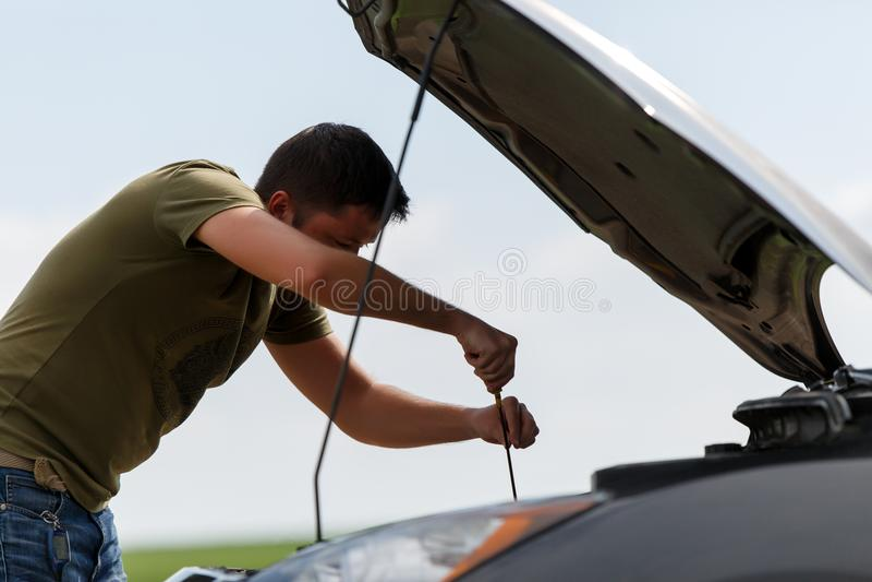 Foto del giovane che ripara automobile tagliata con il cappuccio aperto immagine stock libera da diritti