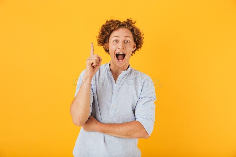 Foto del giovane stupito 20s che grida e che indica upwa del dito immagini stock libere da diritti