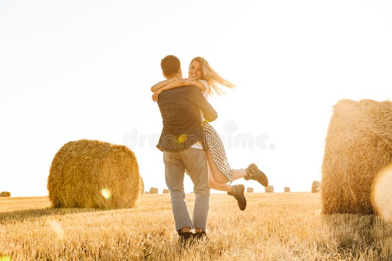 Foto del hombre alegre y de la mujer de los pares que caminan a través de campo de oro imagen de archivo libre de regalías
