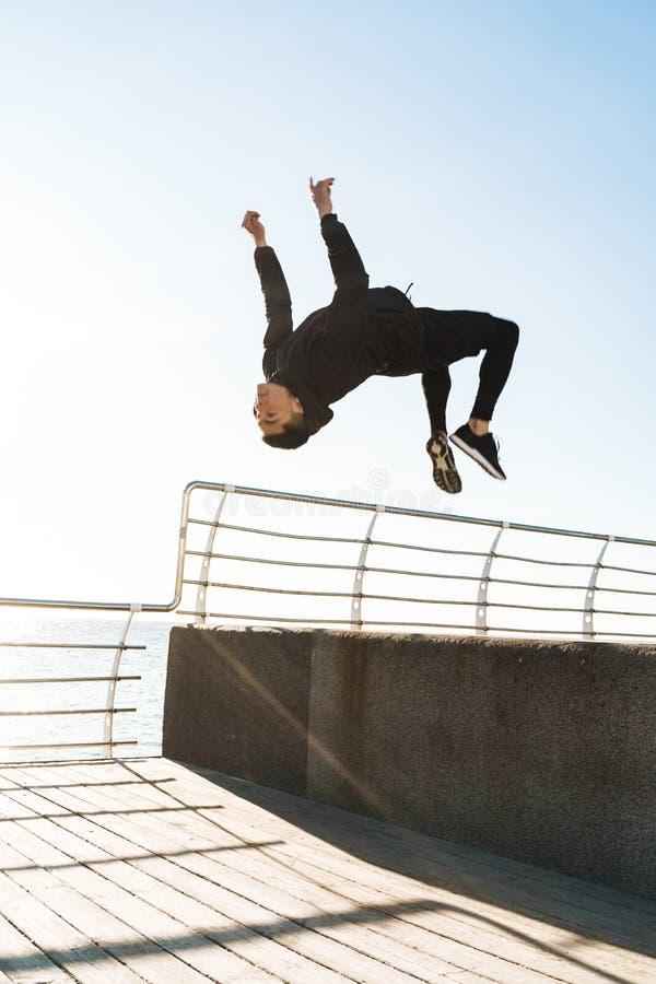 Foto del hombre atlético que hace la acrobacia y que salta durante entrenamiento de la mañana por la playa fotos de archivo libres de regalías