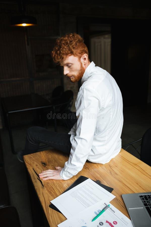 Foto del hombre barbudo rizado del readhead cansado, sentándose en etiqueta de madera imagen de archivo libre de regalías
