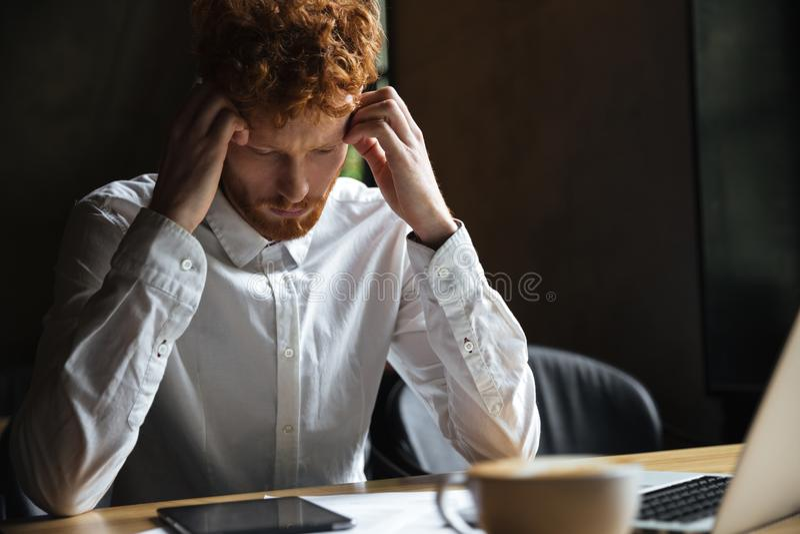 Foto del hombre de negocios cansado del readhead, tocando su cabeza, mirando fotografía de archivo libre de regalías