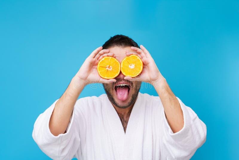 Foto del hombre en la capa blanca con las naranjas cerca de ojos foto de archivo libre de regalías
