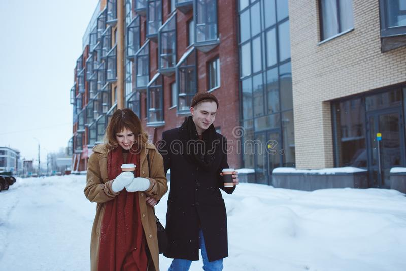 Foto del hombre feliz y de caminar bonito de la mujer al aire libre a lo largo de la calle fría del invierno fotos de archivo libres de regalías