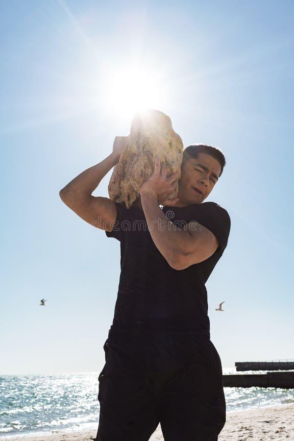 Foto del hombre moreno muscular que camina a lo largo de la playa por la playa y de la piedra grande que lleva en sus manos imágenes de archivo libres de regalías