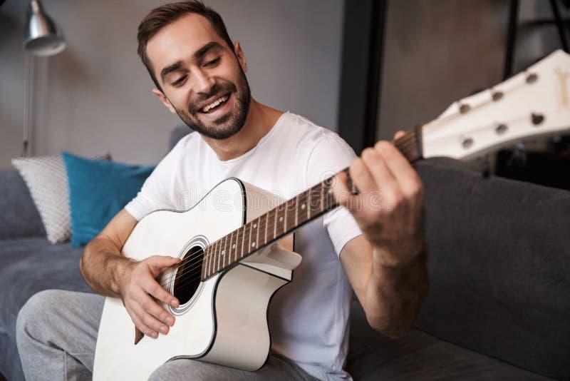 Foto del hombre moreno que toca la guitarra acústica mientras que se sienta en el sofá en el apartamento fotografía de archivo