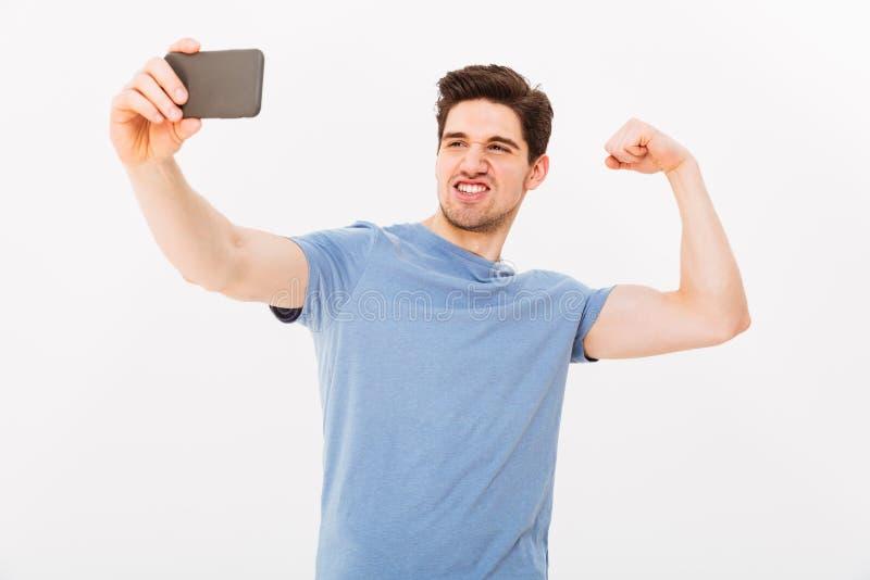 Foto del hombre muscular fuerte en la camiseta que muestra el bíceps en cámara fotos de archivo libres de regalías